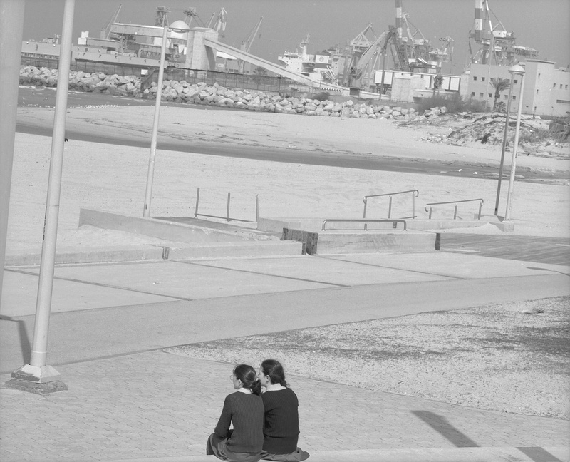Bild von Sharon Ya'ari : 2 Frauen sitzen an ener Uferpromenade in einem Strand- oder Hafenbereich. Schwarzweissaufnahme.