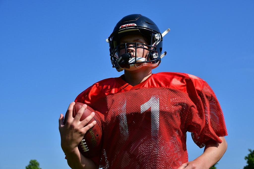 Portrait American Footballspieler in Montur und mit Football. Zum Artikel: Hilfe – mein Kind ist ein Quarterback!