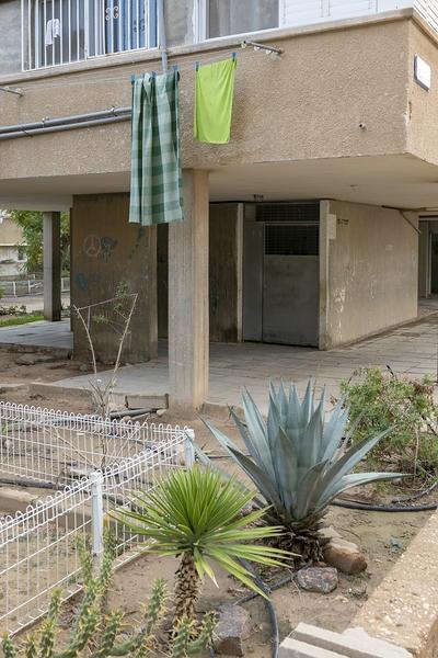 Bild von Sharon Ya'ari: Haus und Vorgarten mit einer Wäscheleine vor dem Balkon. Auf der Leine hängen zwei grüne Tücher