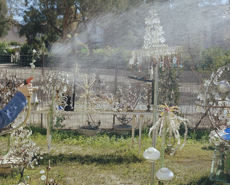 Bild von Sharon Ya'ari : Jemand bewässert seinen Vorgarten, in dem viele Dekorationen aus Glas stehen.